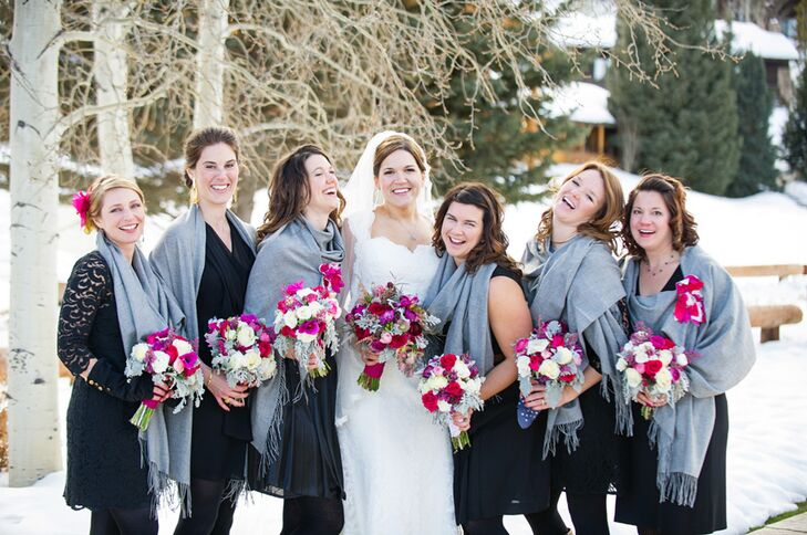 The bridesmaids wore simple black dresses of their choosing with black tights and snow boots. They completed their look with gray scarves to keep warm. To add a pop of color to the otherwise neutral attire, the bridesmaids carried roses, dusty miller and astilbes in shades of pink, purple and ivory.