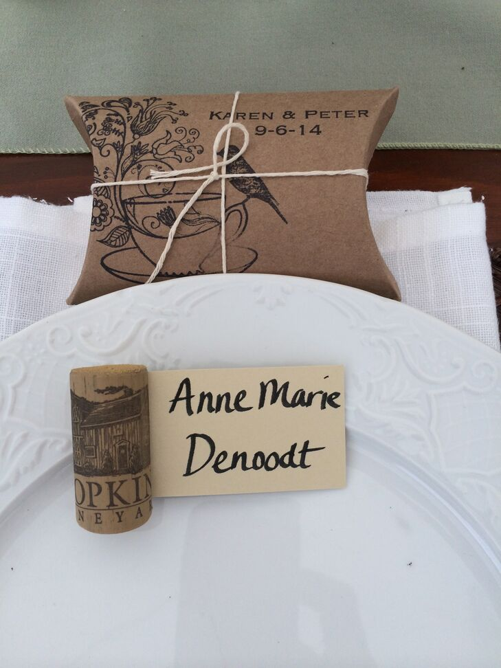 """""""I made the place setting cards using corks from the vineyard, and the favors were Earl Grey tea in hand-stamped pillow boxes,"""" Karen says. """"The table assignments were hand-written cards displayed in an old window, along with photos of both of our parents on their wedding days, and a photo of our cat, who everyone knows we are obsessed with!"""""""