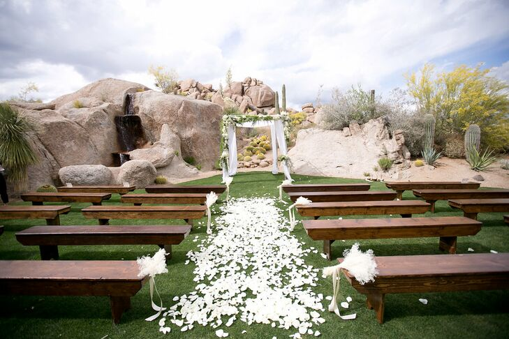Keeping the ceremony decor neutral, only white florals were used: White petals lined the aisle and bundles of white baby's breath sat on wooden ceremony benches. The couple was wed under a white fabric-draped arch lined with white florals and greenery.