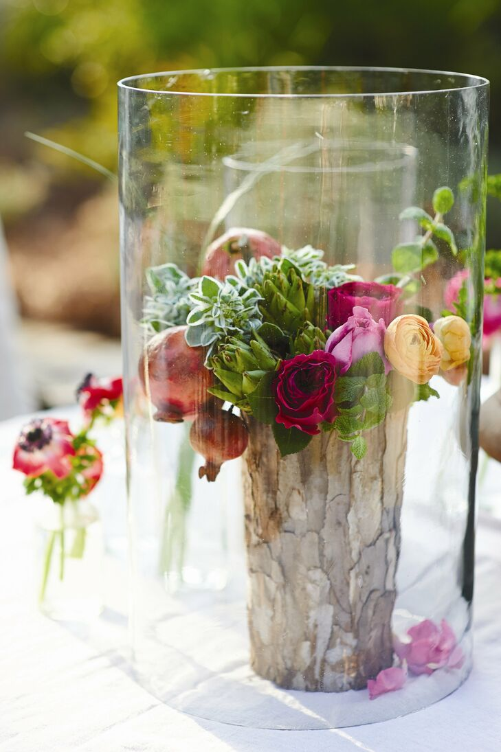 Clear glass jars covered colorful centerpieces of roses, artichokes, ranunculus and pomegranates.