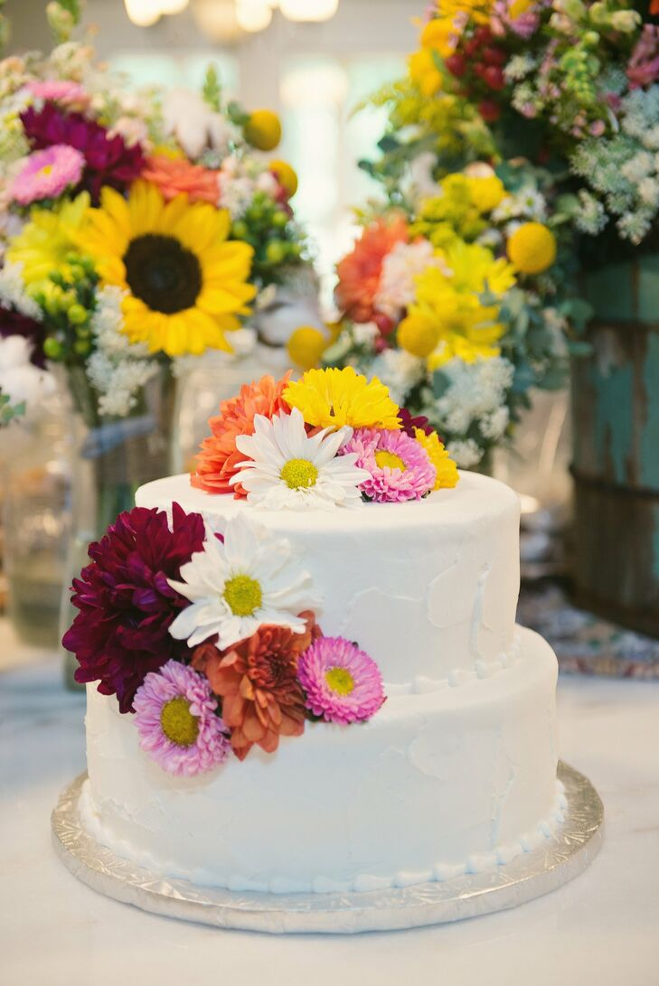 """The wedding cake was a white cake with buttercream frosting called """"Plain Jane"""" and decorated with the same flowers that were in the bridal bouquets. Guests could also taste mini cupcakes and cake balls in Red Velvet, Peanut Butter Cup, Triple Chocolate, Strawberry with White Chocolate, Orange and Margarita flavors."""