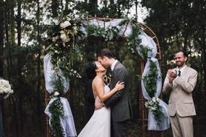 Couple's First Kiss Under Rustic Wood Circle Arch