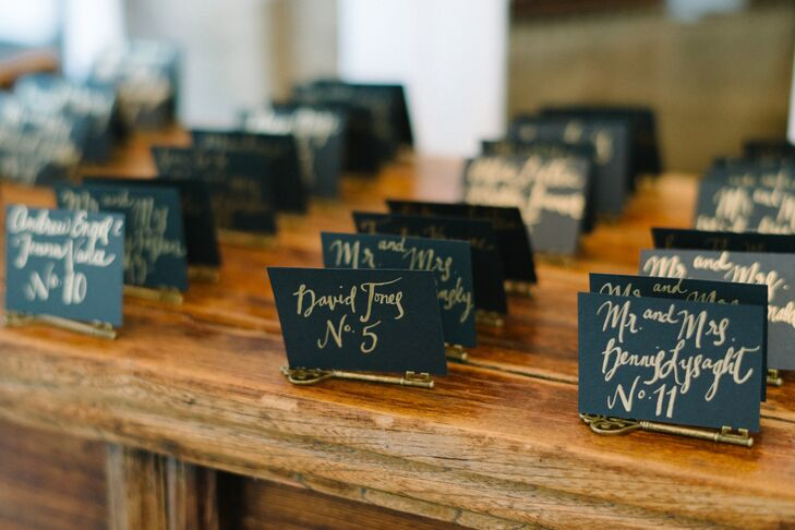 Sarah ordered black escort cards from Paper Source and wrote each guest's name in gold calligraphy. Of course, no one can get into Wonderland without a key. So she paired the notes with matching, gold vintage-style keys.
