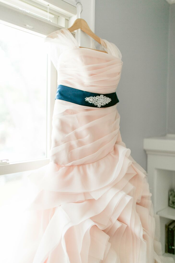 """Mary wasn't wasn't seeking a specific type of wedding gown but wanted more than a traditional white dress. She saw a strapless organza blush trumpet-style Vera Wang when it initially debuted, and it left an impression. After she tried it on, """"the color and feel were perfect,"""" she says, adding that no other dress compared. She bought the matching blush veil and used a portion of the material to create small cap sleeves, then added a navy belt to match the bridesmaid dresses."""
