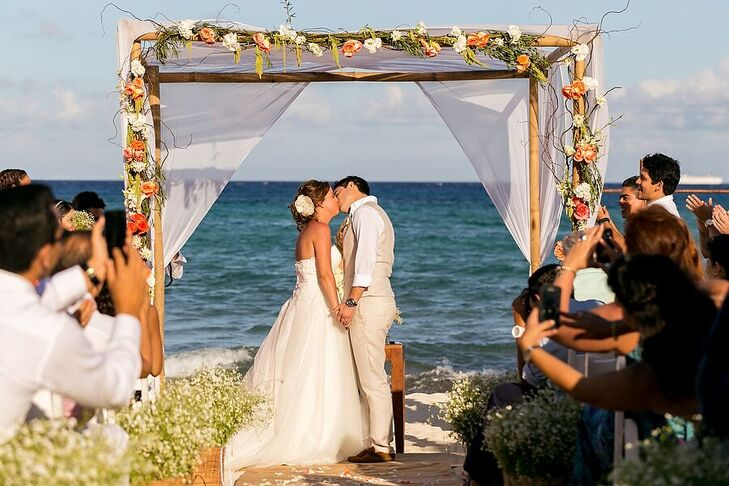 At their beach ceremony, Marta and Jose Luis stood under a wooden arch draped with white linens. Whimsical branches, green hanging amaranthus and white and coral flowers added a romantic touch.