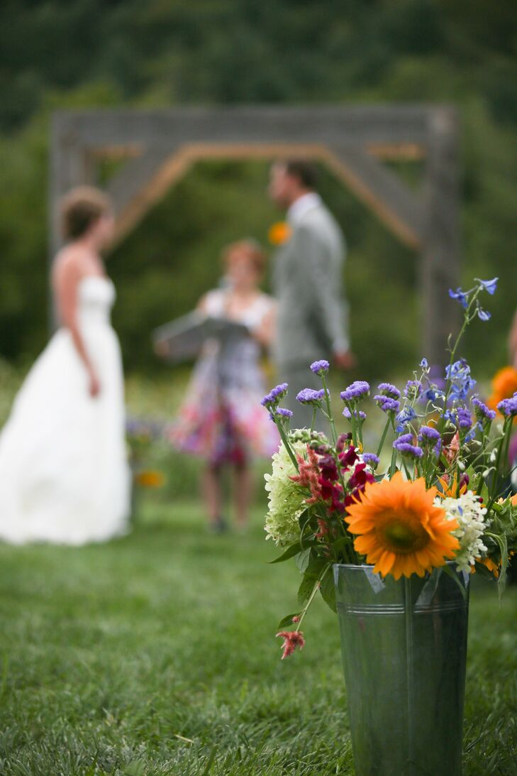 Colorful wildflowers filled dark green watering cans and were placed at the end of each aisle.
