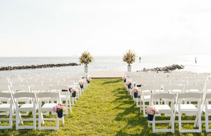 The ceremony took place right on the water, where white garden chairs and pails of pink blooms added subtle color to the already stunning location.