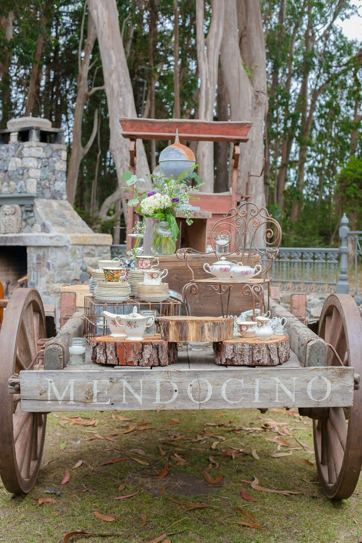 A vintage wooden cart held china cups and plates for guests.