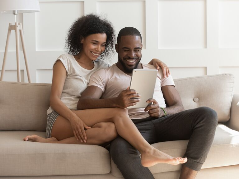 Couple sitting on the couch and looking at a tablet