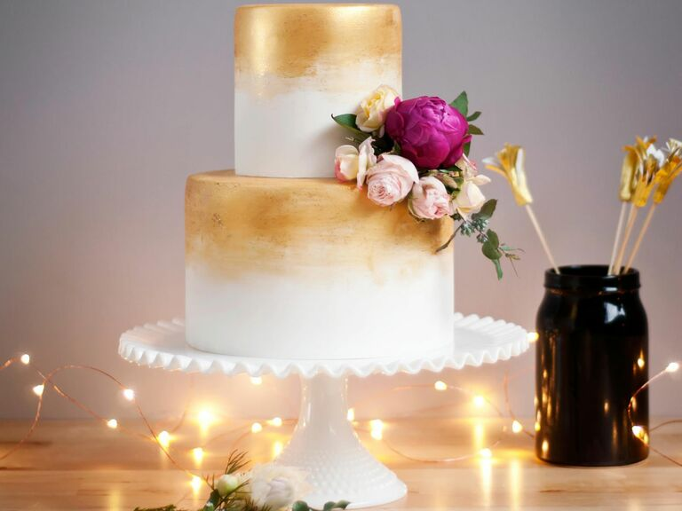 White wedding cake brushed with edible gold paint.