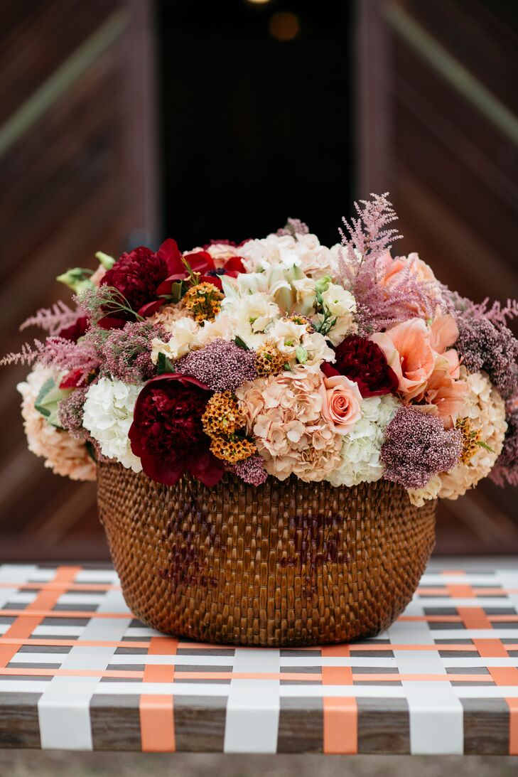 A mix of pink astilbes, roses, hydrangeas and peonies in a woven basket served as decor.