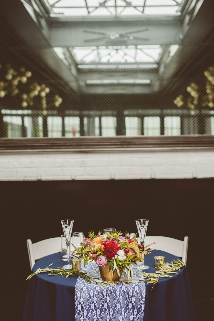 A lush centerpiece arrangement of dahlias, thistle, ranunculuses and eucalyptus leaves decorated the sweetheart table.
