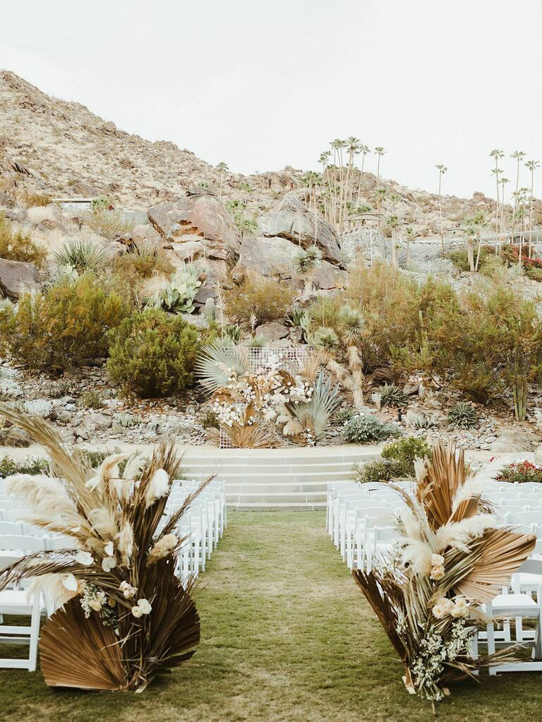 Bohemian wedding ceremony aisle in front of desert mountains with pampas grass flowers