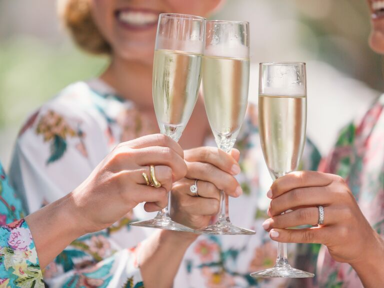 Bridesmaids toast champagne in matching floral robes