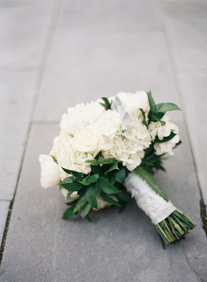 To achieve her dream bouquet of large white blooms, Nina carried ranunculus, garden roses, peonies and hydrangeas along with some greenery and dusty miller. The bridesmaid bouquets were small bouquets of white garden roses and hydrangeas with a bit more greenery than Nina's, and the boutonnieres consisted of white ranunculus with greenery accents.