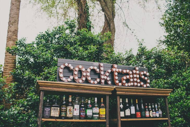 "To display beverage choices to their guests, Katie and Derick had each wine, beer and liquor option set out on a distressed wooden shelf under a funky wooden ""cocktail"" sign. Letters were roughly cut and assembled in a relaxed, jagged manner."