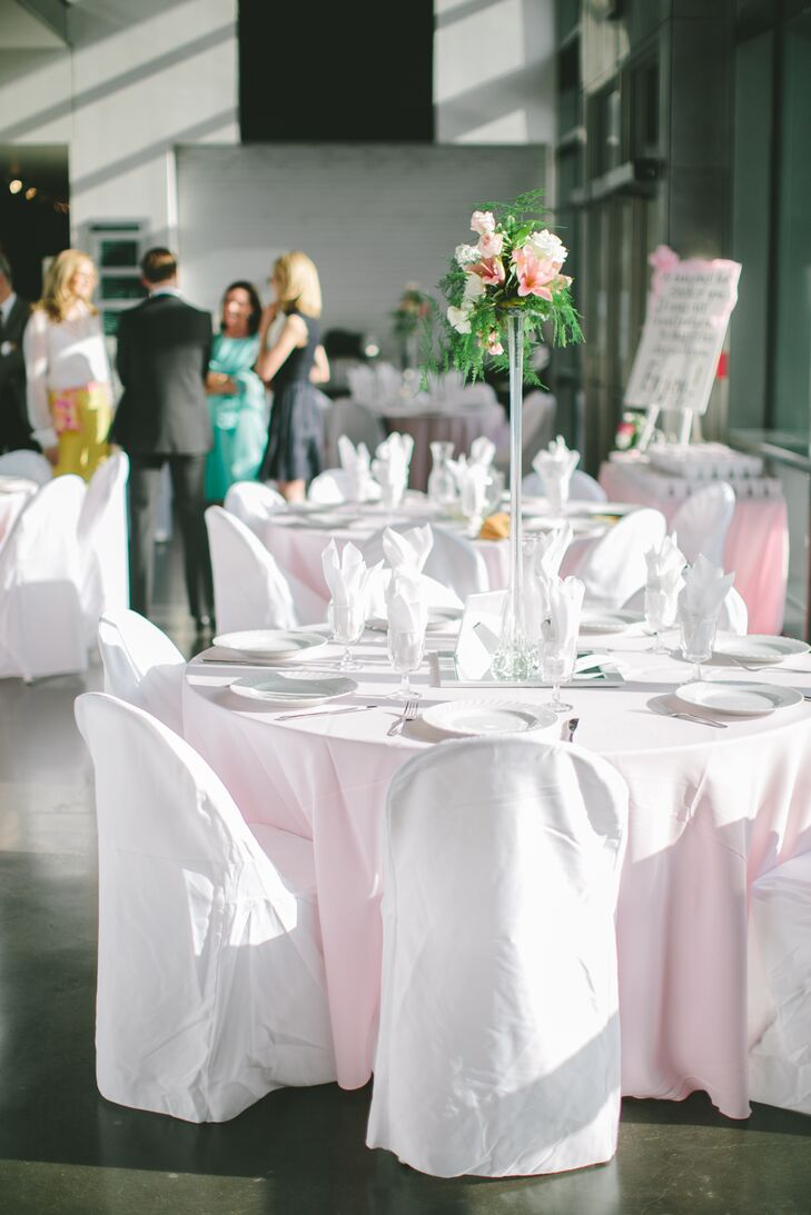 The reception tables were topped with light pink linens and towering centerpieces including green pine, pink lilies and white roses. Since Lawrence Art Center is really modern, they decided to use sleek details such as contemporary vases and mirrors to complement the room.