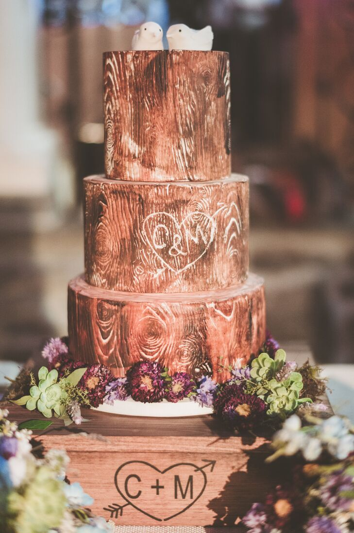 Tying in with the evening's rustic theme, the couple's wedding cake featured a charming woodland design. The three-tier confection was adorned with a hand-painted wood-grain pattern, purple wildflowers and petite bird cake toppers.