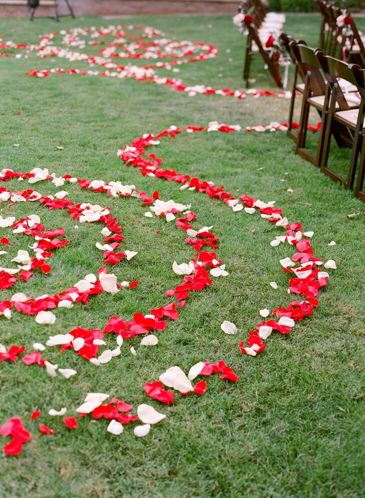 Red and white rose petals were formed into swirling shapes on the grass leading up to ceremony seating. Two lines of petals continued down the aisle.