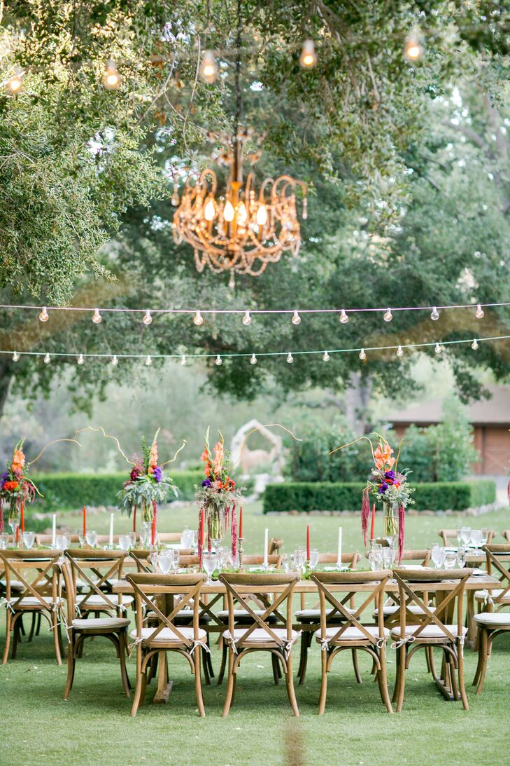 "String lights and chandeliers added warmth and glamour to the outdoor reception at Oak Canyon Ranch in Cornell, California. ""To go with the elegant chandeliers, we added touches of gold in brass candleholders and chargers,"" Lisa says. ""We truly felt that this wedding was going to be a dream come true, and it was. It was the epitome of rustic elegance."""