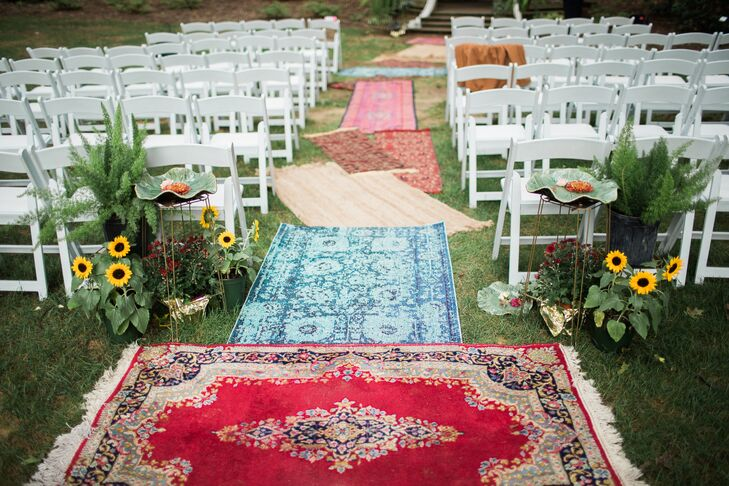 Overlapping, colorful rugs functioned as an eclectic aisle runner and brightened the organic ceremony space.