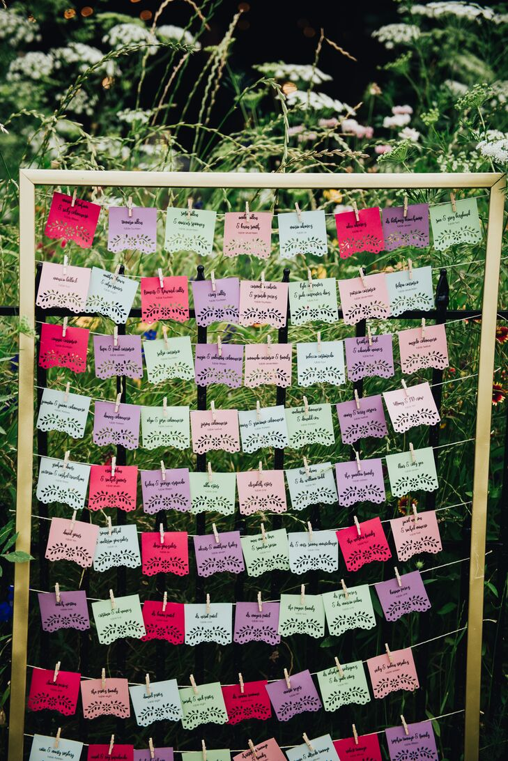 Escort cards were printed on purple, pink, blue and green cards with a floral eyelet cutout, then safety-pinned to string fastened to a wooden frame.
