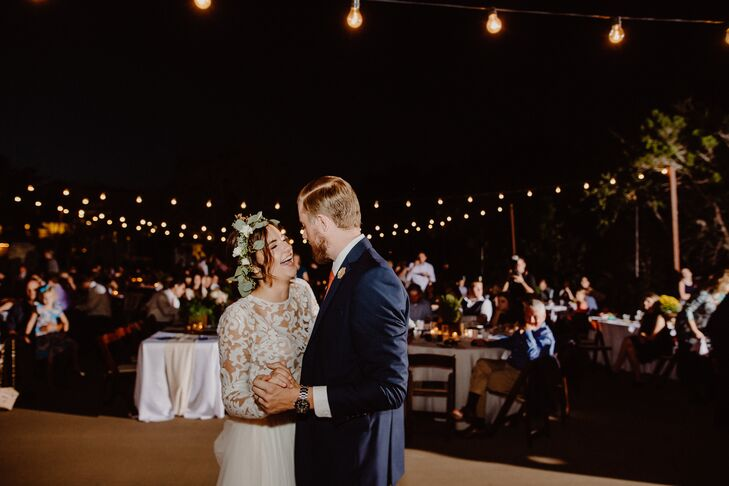 Emily and Jonathan dance under string lights on the outdoor dance floor at the Greenhouse at Driftwood in Driftwood, Texas.