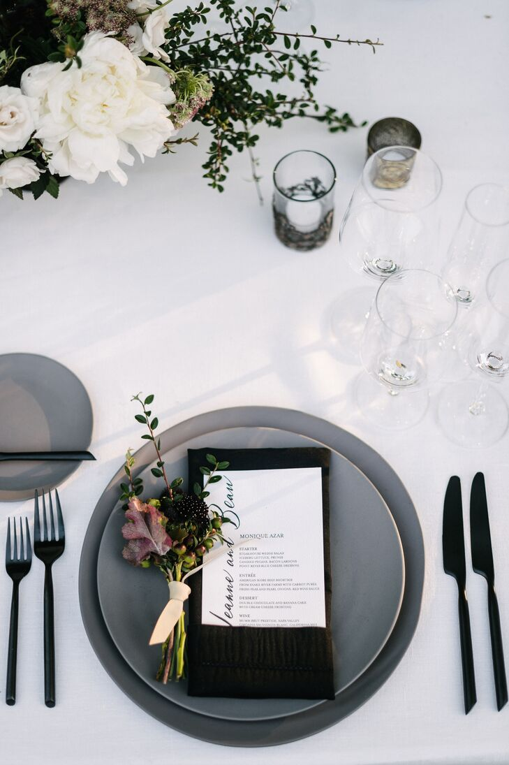 Gray plates and chargers were contrasted with black flatware and a crisp white linen table cloth. Centerpieces were a mix of light and dark blooms.