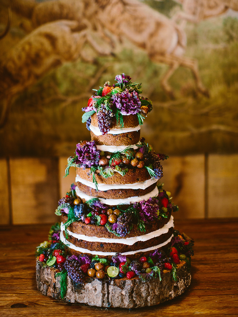 rustic naked wedding cake with purple flowers and fruit