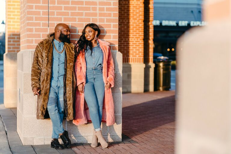 Couple smiling at each other while wearing denim outfits and coats