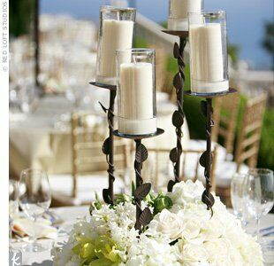 On some tables, wrought-iron candlesticks held pillar candles above dense arrangements of hydrangeas, orchids, and roses for a Mediterranean vibe. The look went with the wedding's Tuscan-style villa location.
