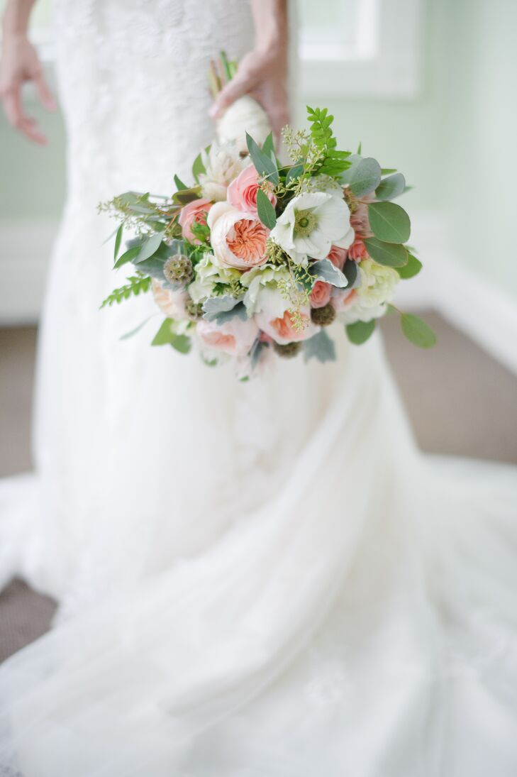 "Erica carried a hand-tied lush bouquet of blush garden roses, white anemone, dusty miller, scabiosa pods and eucalyptus down the aisle. ""The bouquet was tied with an ivory satin wrap and my maternal great grandmother's cameo was pinned to the wrap,"" says Erica. ""It was very special and sentimental to my mother and myself."""