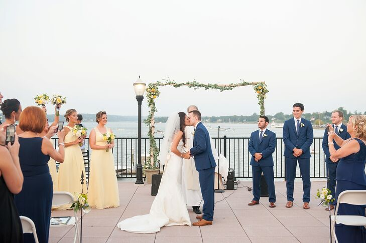 """""""The day we decided to have the Molly Pitcher Inn as our venue, we stepped outside on the promenade and were stunned by the beauty of all the boats on the river,"""" Pam says. She and Sean were surrounded by the same view, as they shared their first kiss. Highlighting the location, they chose only natural decor. A chic garland-wrapped birchwood arch marked the ceremony space."""