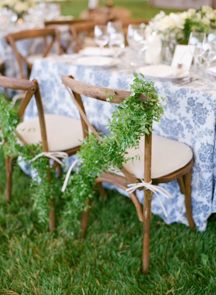 The bride and groom chose wooden chairs to achieve a rustic style, and decorated their two chairs with natural green garlands.