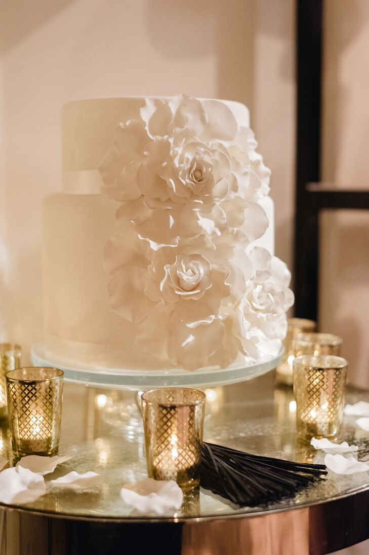 The all-white, two-tier cake was decorated with a large white sugar flower and cascading flower petals down the side.