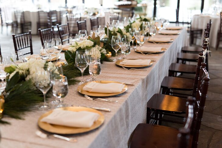 The wedding party members and their dates sat at a long table that was in the center of the reception space. it was topped with gorgeous flower arrangements, including white hydrangeas and seasonal green pine. Gold mercury glass votives and the gold chargers added the perfect amount of glamour.