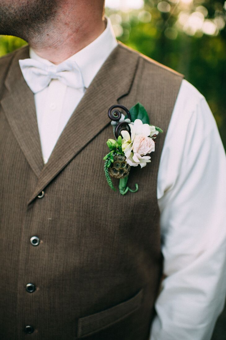 Kim and her bridesmaids weren't the only ones with chic, garden-style accents. Nick stepped into the ceremony with a natural arrangement upon his neutral vest. Designed by Ibranyi Is Floral, its green wrap contained silver brunias, bold fiddlehead ferns, white veronica and scabiosa. A white carnation marked the center alongside leaves for texture.