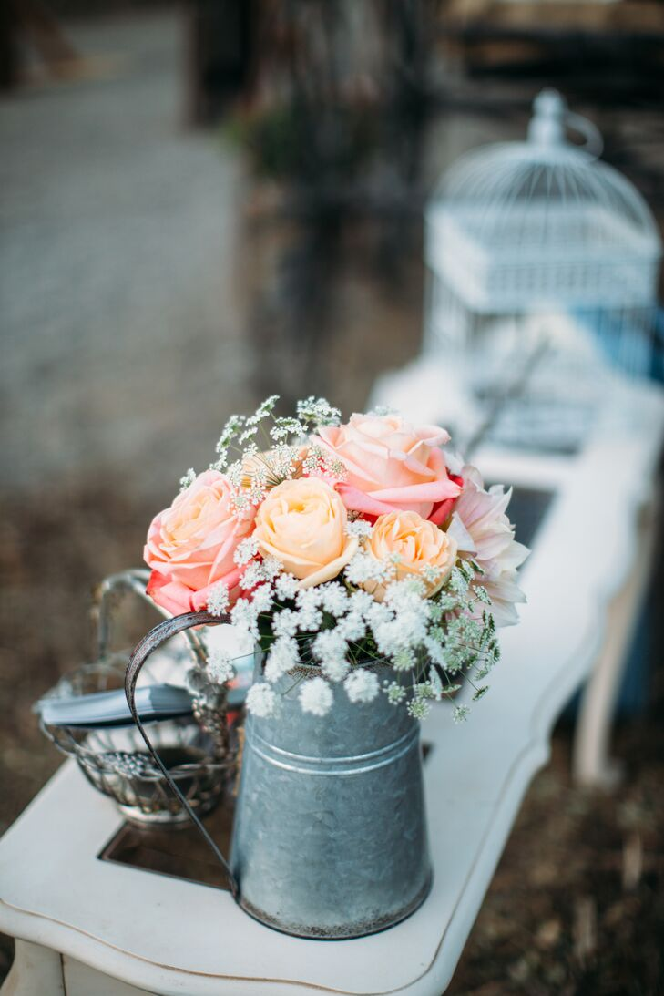 Peach and coral roses mixed with Queen Anne's lace filled a tin pitcher, which added to the overall shabby-chic vibe. Many similar flower arrangements filled with soft-colored blooms made an appearance at the wedding as well.