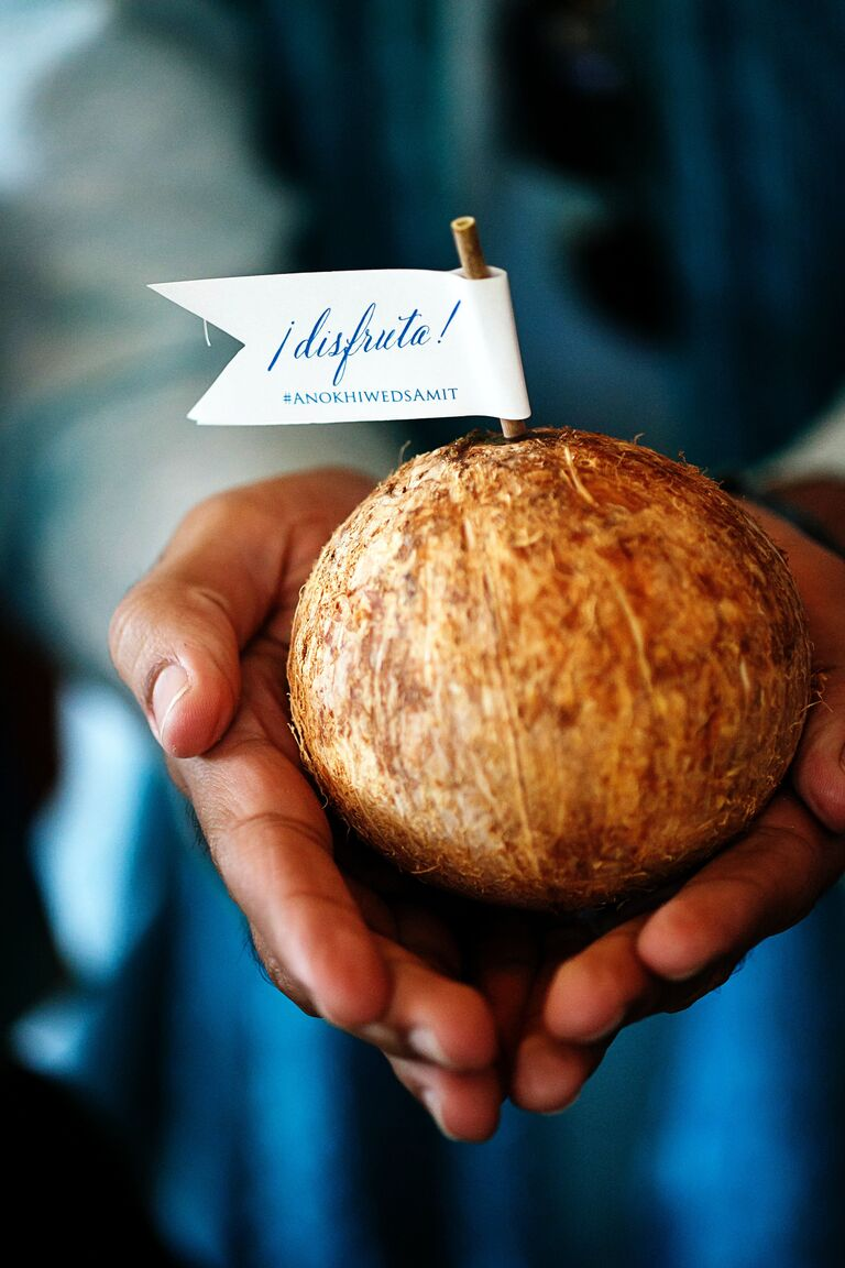 Fresh coconut wedding guest favor with straw and flag