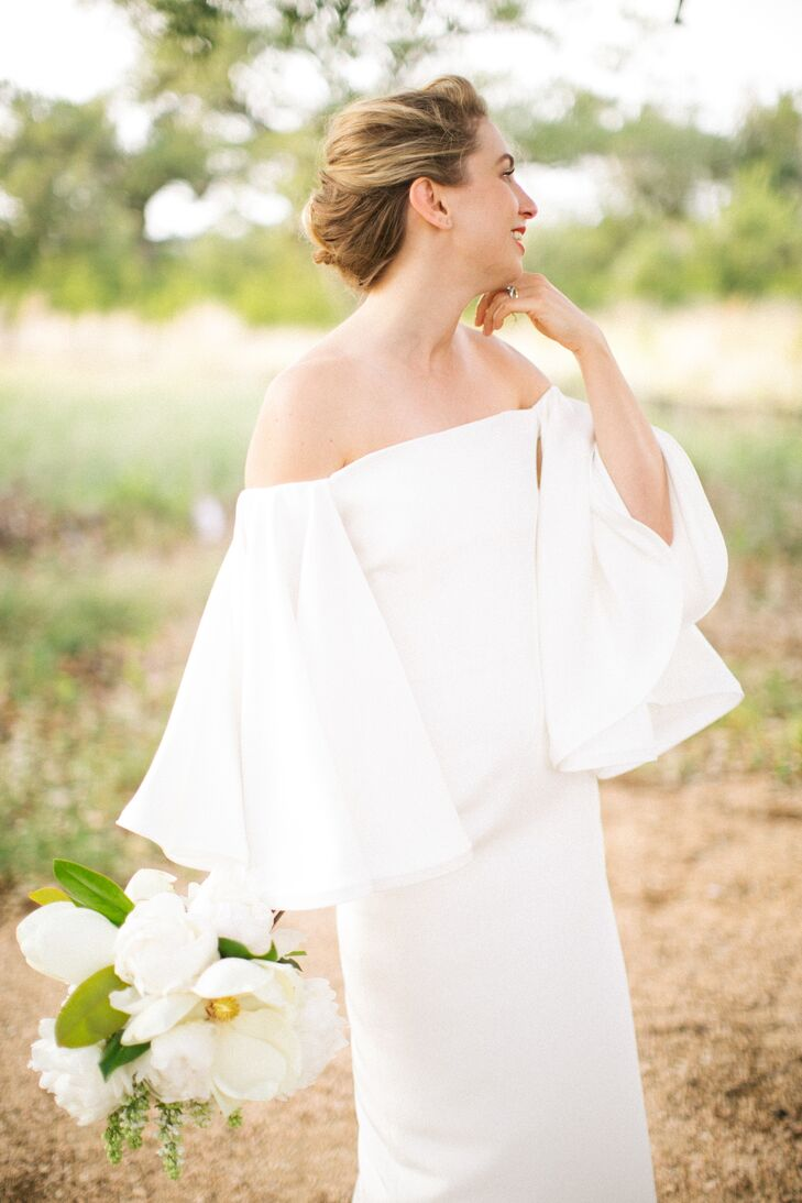 Sleek Bell-Sleeve Sheath Bridal Gown And All-White Magnolia Bouquet