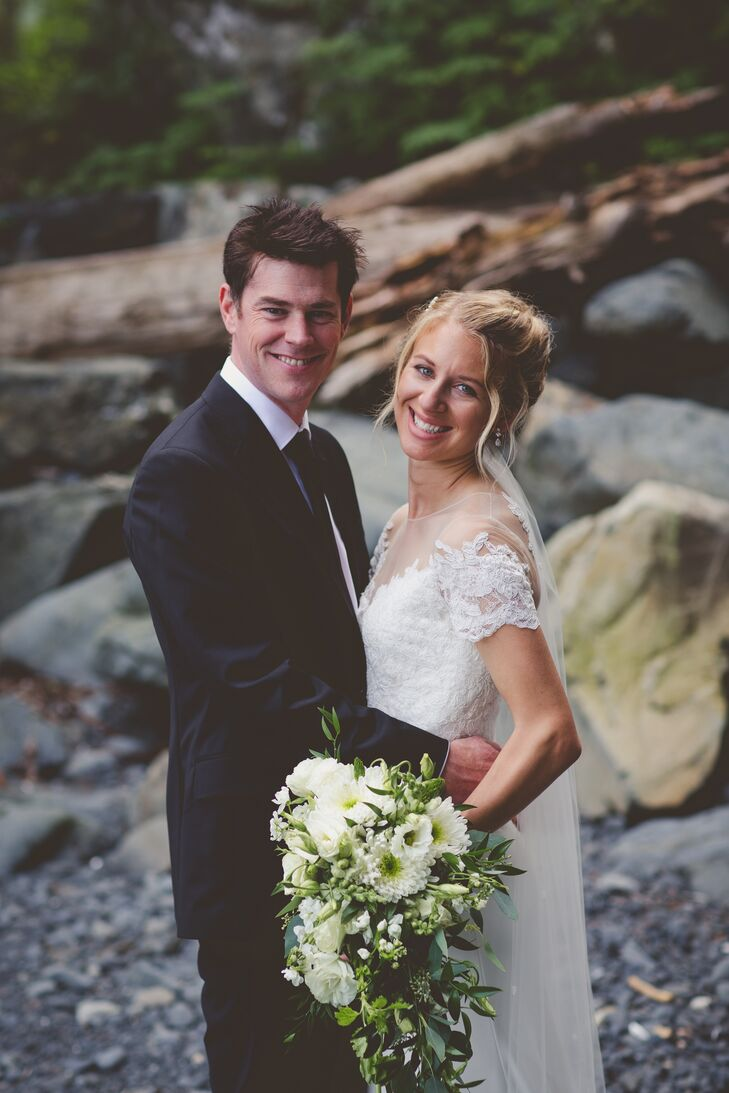 """Joe wore a black suit with Xtratuf boots, while Megan donned a gown with organically inspired details. """"The lace looked like vines, which fit the setting,"""" Megan says. """"The dress also fit my requirements: I wanted to be able to lift my hands, walk in boots and get in and out of a boat."""""""