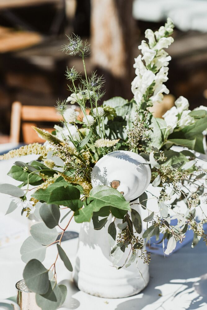The centerpieces consisted of white flowers and greenery displayed in simple vases.