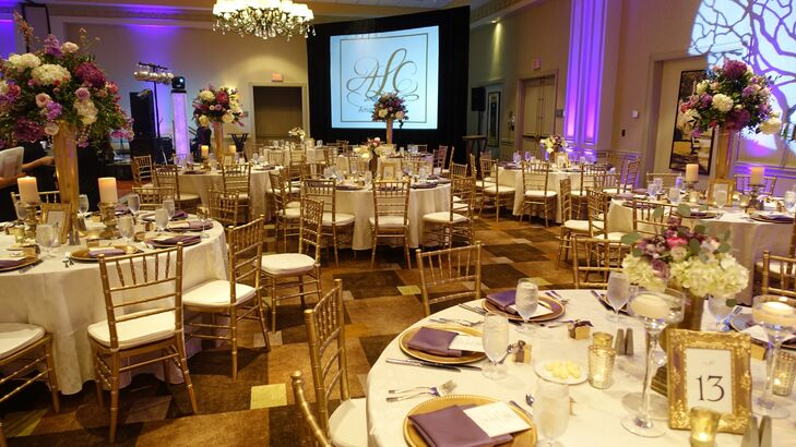 Gold carpeting and purple uplighting framed the Grand Ballroom at Westin Savannah Harbor in Savannah, Georgia, where Amanda and Chris hosted their reception. Their custom monogram was displayed on a screen, which later showed a personalized video of their love story.