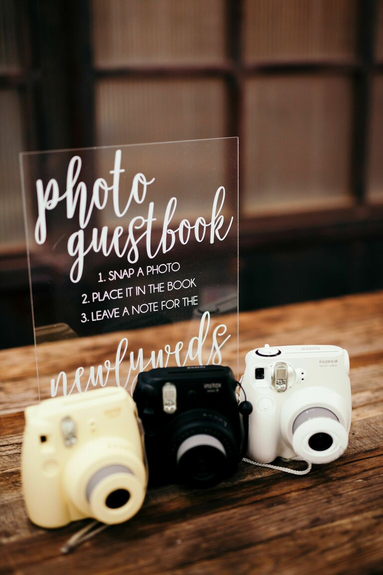 Polaroid cameras sitting on table with acrylic sign