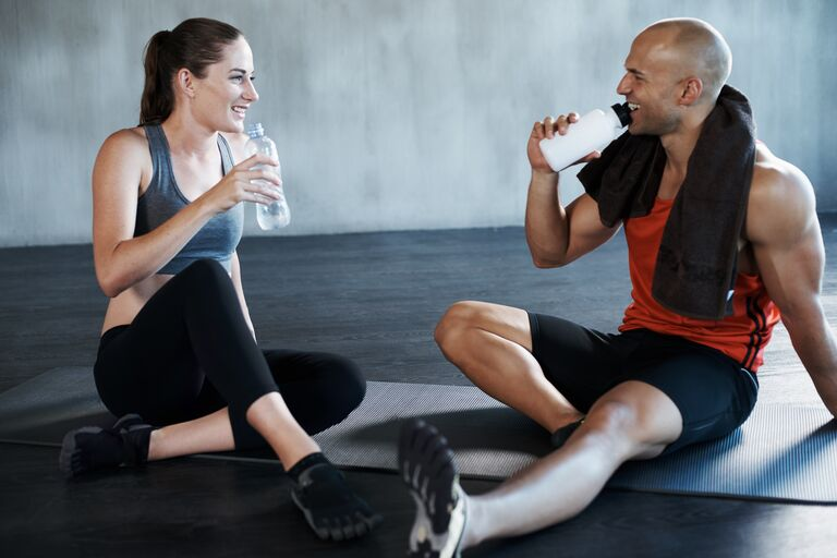 couple hydrating drinking water after fitness