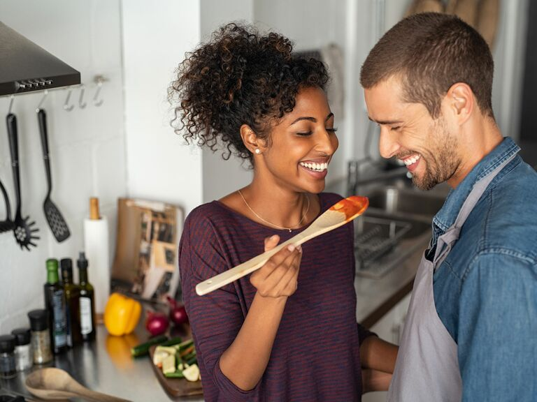 couple smiling tasting homemade sauce in kitchen