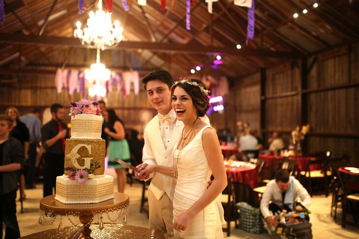 "Dinner finished on a high note with Madelyn and Ryan serving not one but two decadent cakes by Sherlyn Boyd Cakes. The first was a three-tier ivory stunner with a glitzy gold middle layer, bunches of fresh purple flowers and a fondant ""G"" for the couple's last name. Brenda Brashier Cakes provided the second confection, tempting guests' taste buds with a tiered naked cake with fresh fruit and decadent frosting."