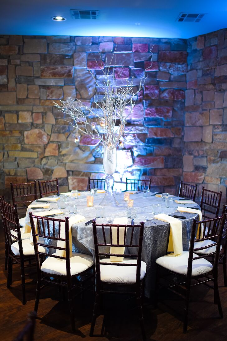 To add height to the space, some of the dining tables were decorated with arrangements of tall silver branches. These centerpieces, combined with the blue uplighting, created a wintry effect.