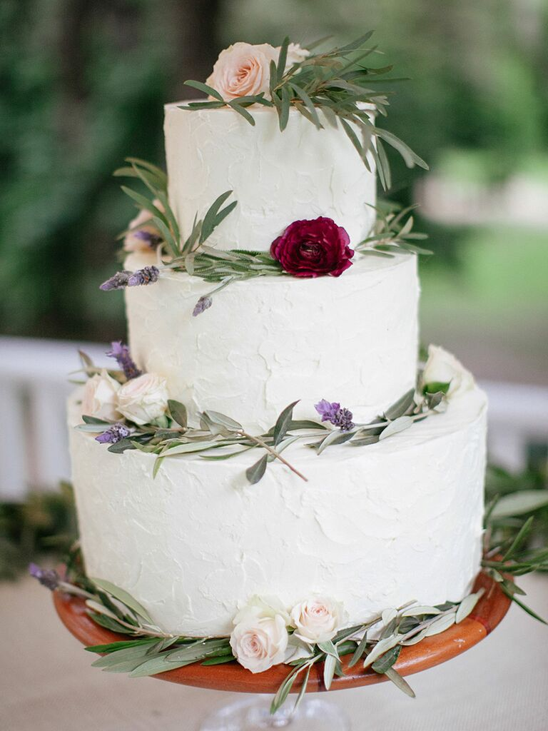Small white wedding cake with greenery, lavender and ranunculus