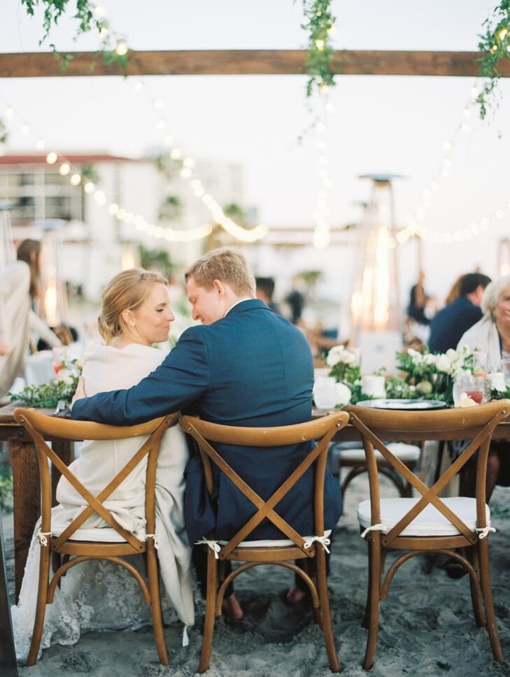 At the seaside reception at Hotel del Coronado in San Diego, California, long banquet tables were topped with simple white linens and illuminated by string lights after the sun went down.